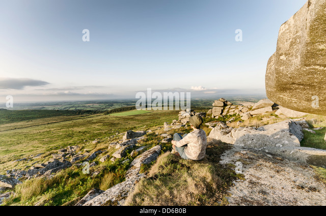 Woman sitting on top of Kilmar Tor on Bodmin Moor in Cornwall, vintage effect. - Stock Image