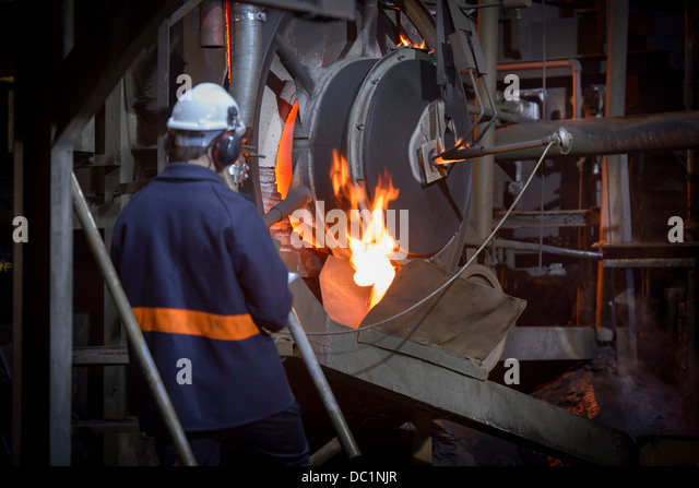Steel worker pouring molten metal in steel foundry - Stock Image
