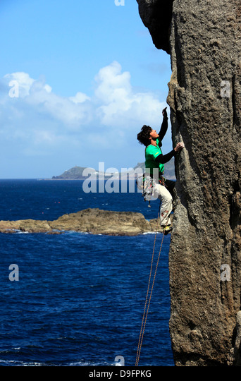 A climber scales cliffs at Sennen Cove, Cornwall, England, UK - Stock Image