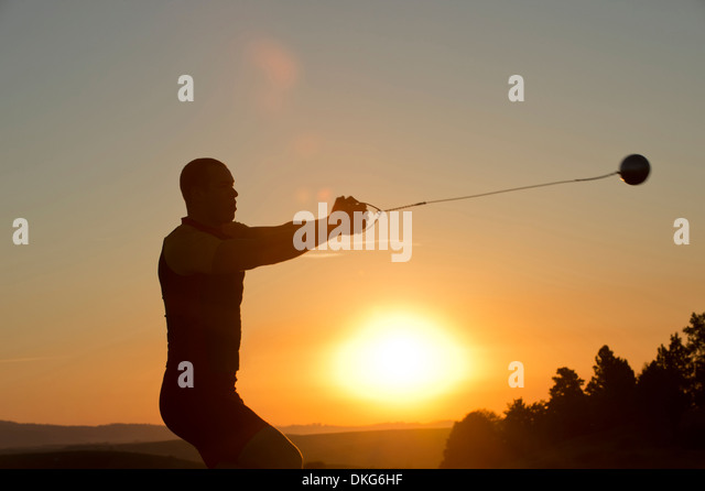 Young man preparing to throw the hammer at sunset - Stock Image