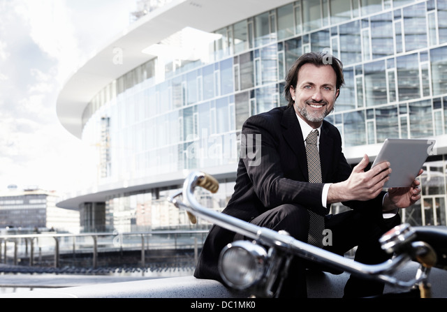 Mid adult businessman using digital tablet in city, portrait - Stock Image