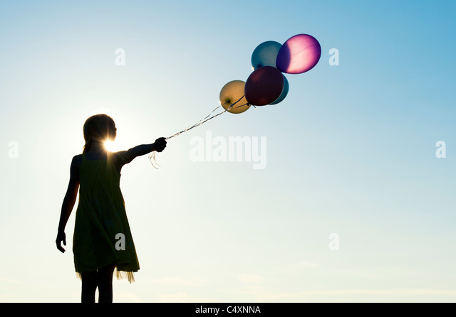 Silhouette of a young girl holding coloured balloons at sunset - Stock Image