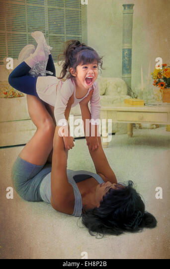 Digital art effects Filipina mom exercising on floor lifts her 3 year years old daughter on her legs MR  © - Stock-Bilder