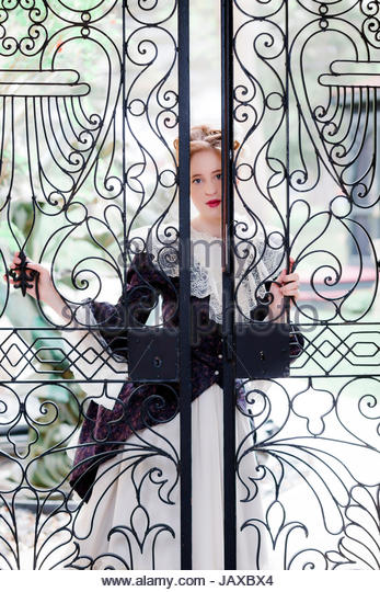 Victorian woman peering through a wrought iron fence gate - Stock Image