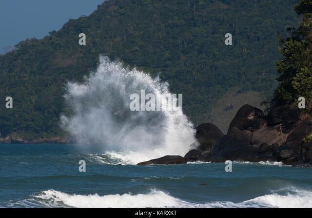 Wave crashing on a rock in Ilhabela, São Paulo, Brazil - Stock Image