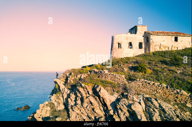 A man standing on a high cliff enjoying the view of an Italian coast with the Mediterranean sea Below him. Porto - Stock Image