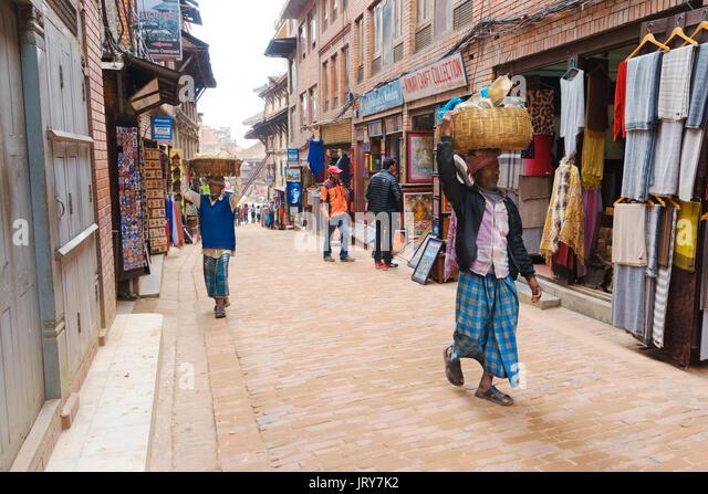 Men delivering merchandise in baskets held on their head. Bhaktapur, Nepal. - Stock Image