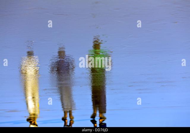 Mozambique, Nampula Province, men walking on shoreline. - Stock Image
