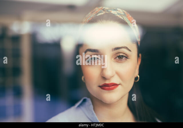 Horizontal portrait of young woman feeling the fatigue and looking at camera. - Stock Image