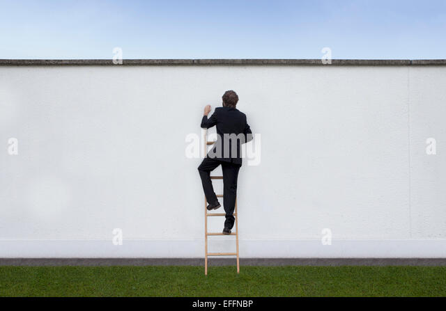 Business man climbing on carrier ladder - Stock Image