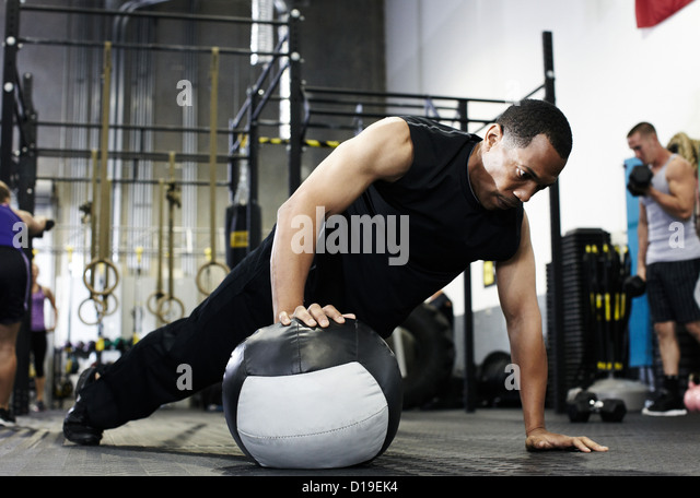 Man doing push up with one hand on medicine ball - Stock Image