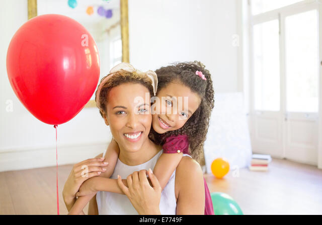 Mother and daughter hugging in living space - Stock Image