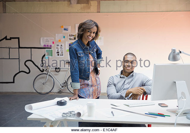 Portrait of confident business people at desk in office - Stock-Bilder
