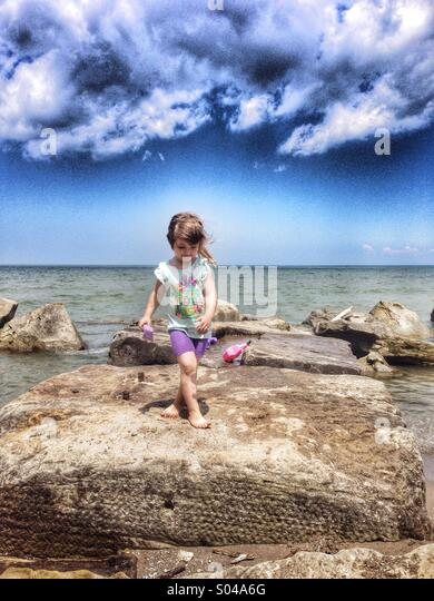Toddler Caucasian girl walks on rocks at beach - Stock Image