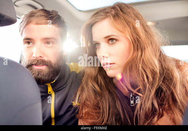Couple on back seat of a car in backlight - Stock Image