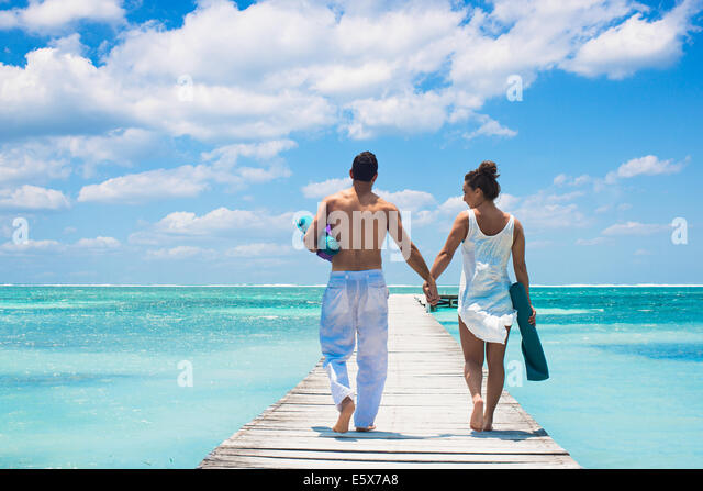 Young couple walking on pier, San Pedro, Belize - Stock Image