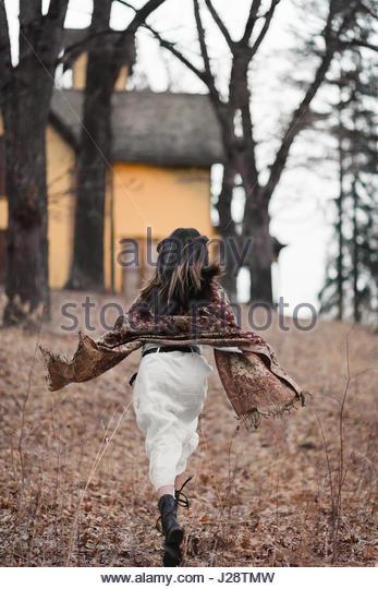 Brunette woman running away - Stock Image