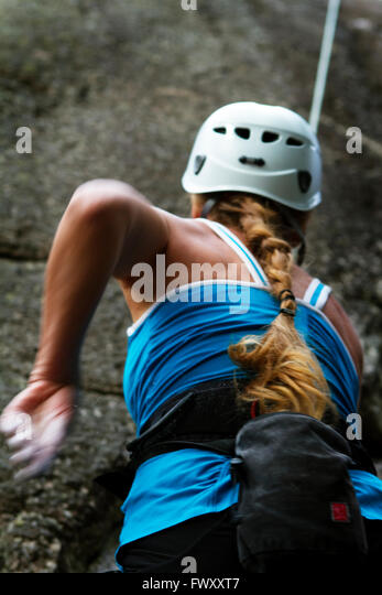 Sweden, Ostergotland, Vaderstad, Rear view of woman climbing rock - Stock Image