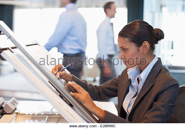 Businesswoman drawing on drafting table in office - Stock Image