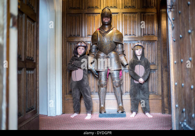 Two boys  in onesies standing next to a knight in armour at Thornbury Castle. - Stock Image