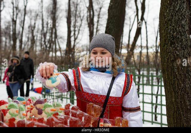 St. Petersburg, Russia, 26th February, 2017. Woman selling sweets on stick during Shrovetide celebrations in the - Stock Image