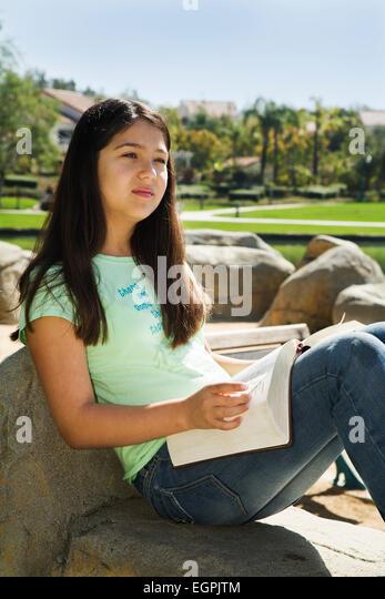 Vietnamese-Caucasian children  teen girl 11-13 years old reading Bible meditating  multi racial diversity racially - Stock-Bilder