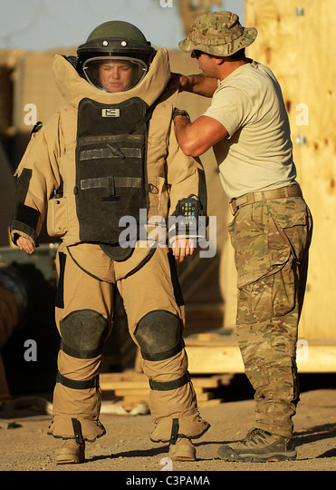 US Army soldier readies her protective bomb suite as the bomb disposal unit prepares to disarm an IED in Afghanistan. - Stock Image