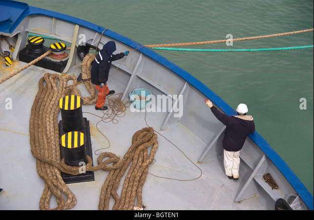 Ship's crew on the bow of a ship involved in mooring operations after arrival in port. - Stock Image