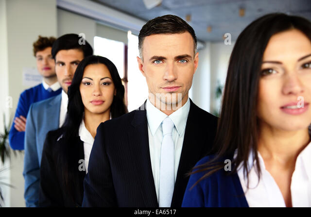 Group of a serious business people standing in a row in office - Stock Image