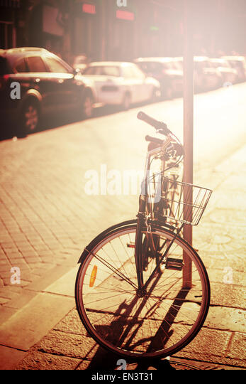 Bicycle resting at the street. Instagram effect, image toned in vintage colors. Selective focus. - Stock Image