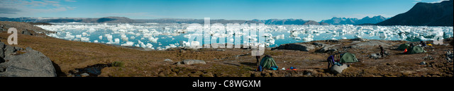A panorama of Sermilik Fjord, East Greenland with a trekking group camped in the foreground. - Stock Image