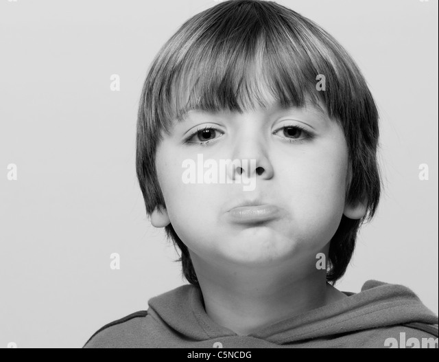 Portrait of a young boy, sulking - Stock Image