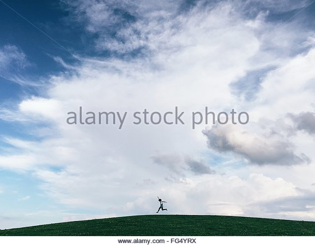 Man Jumping On Field Against Sky - Stock Image