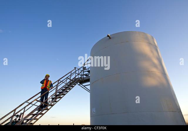 Oil industry worker on storage tank platform talking on phone. - Stock Image