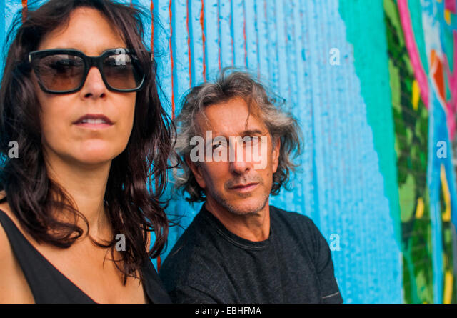 Portrait of cool mature couple in front of graffiti wall - Stock-Bilder