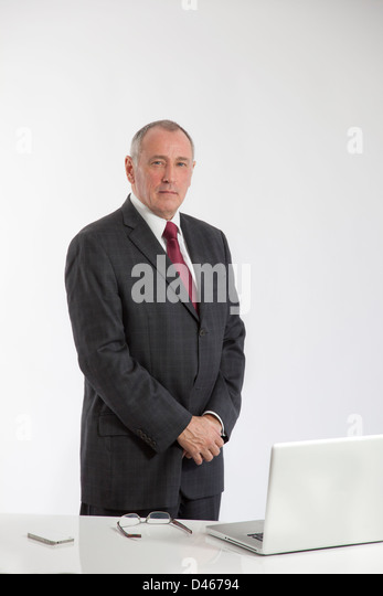 Portrait of a mature male office worker standing behind a white desk with a laptop open, glasses and iphone on the - Stock-Bilder