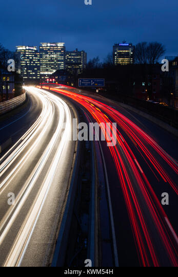 Light trails on Autobahn A40 motorway with the Essen skyline at the back, Essen, Ruhr Area, Germany - Stock Image