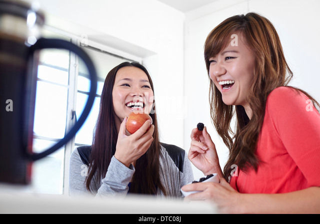 Two young women in kitchen eating fruit - Stock Image