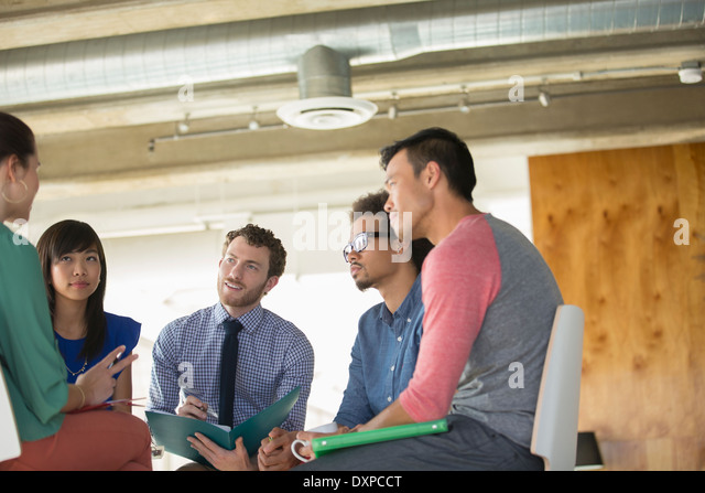 Creative business people meeting in circle of chairs - Stock Image