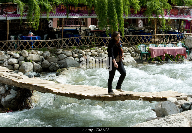 Crossing over a raging river on a precarious wooden slatted bridge in Setti Fatma, Ourika Valley, Morocco, North - Stock Image