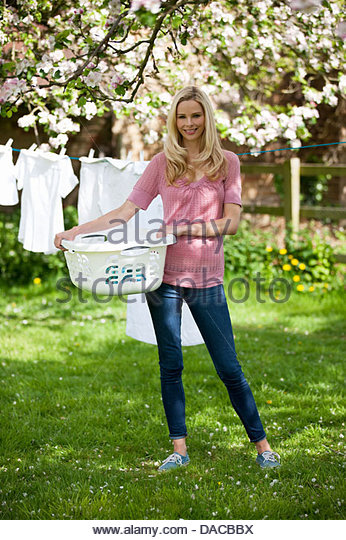 A young woman holding a washing basket in front of a washing line - Stock Image