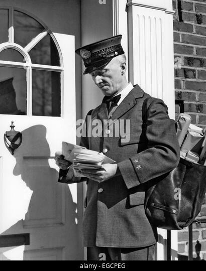 1930s 1940s POSTAL SERVICE UNIFORMED MAILMAN DELIVERING MAIL STANDING ON DOORSTEP SORTING LETTERS - Stock Image