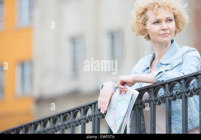 Thoughtful middle-aged woman holding map while leaning on railing - Stock Image