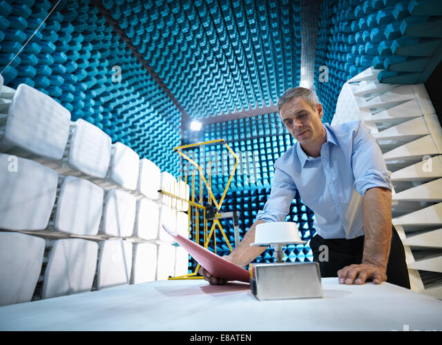 Scientist preparing to measure electromagnetic waves in anechoic chamber, low angle view - Stock-Bilder