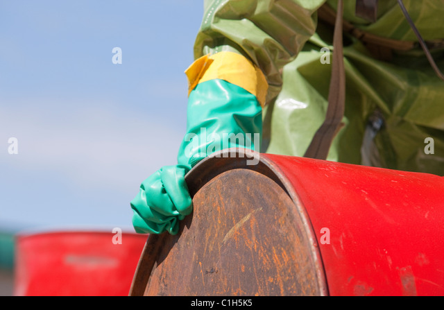 HazMat firefighter moving a chemical drum - Stock Image