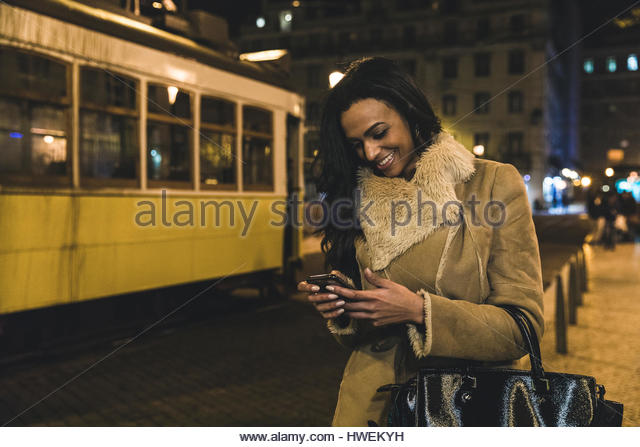 Young woman in city at night, using smartphone, Lisbon, Portugal - Stock-Bilder