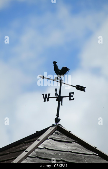 A weather vane on the roof of a building, pointing South-West - Stock Image