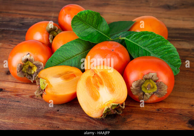 ripe persimmons kaki fruits on rustic background - Stock Image