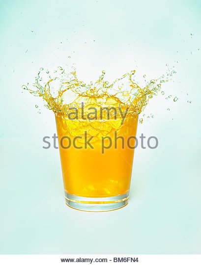 Close up of orange juice splashing out of glass - Stock Image