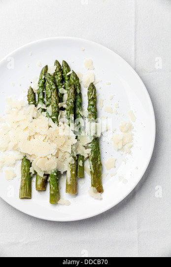 Asparagus with Parmesan cheese on white background - Stock Image